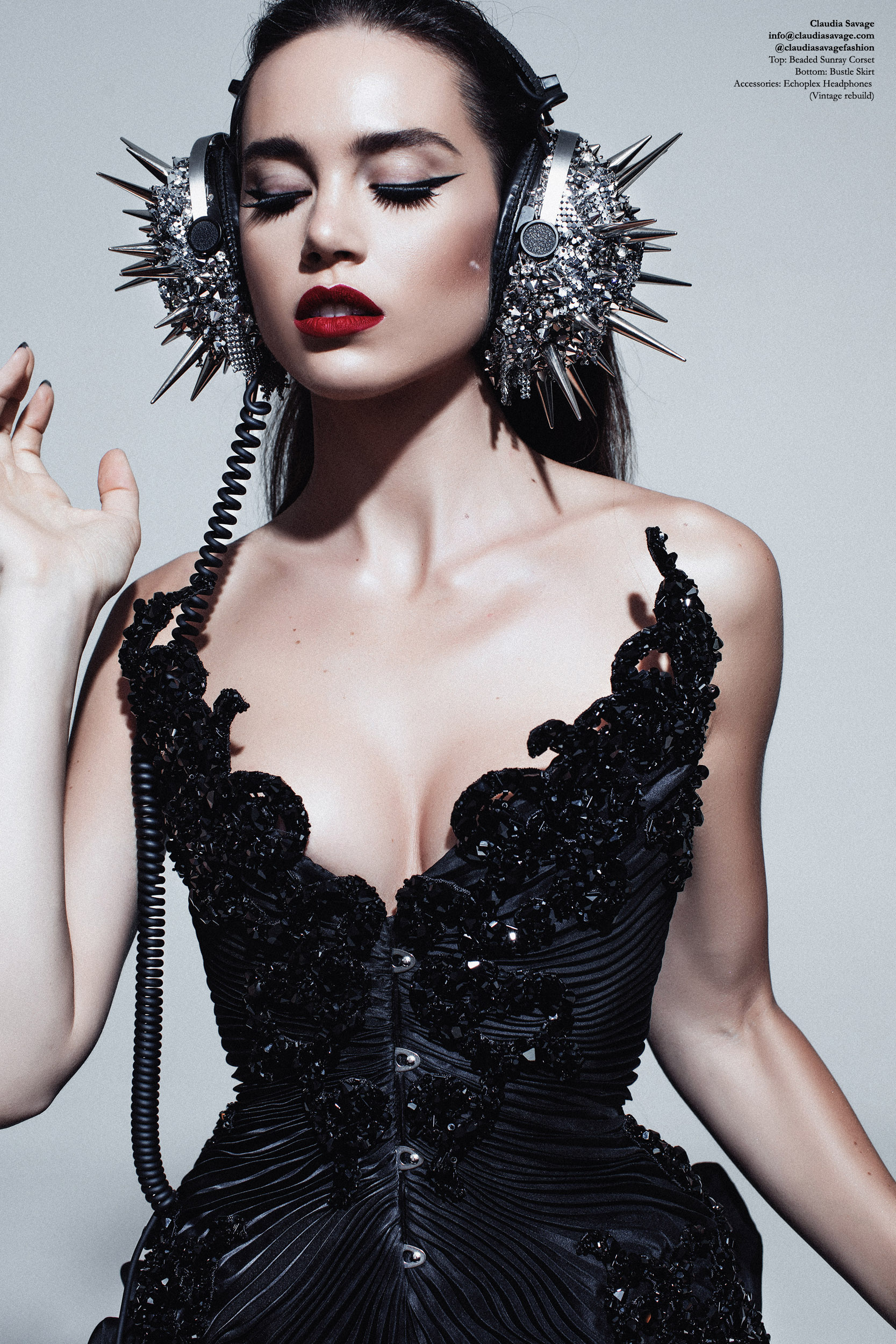 """Model wears a made to measure corset with black silk organza pleating, encrusted with sculptural lace which has been coated in hand stitched jet Swarovski Elements. The silver """"Echoplex"""" headphones are coated in silver coloured studs and spikes, draped in metallic mesh and hand encrusted with silver Swarovski Elements."""