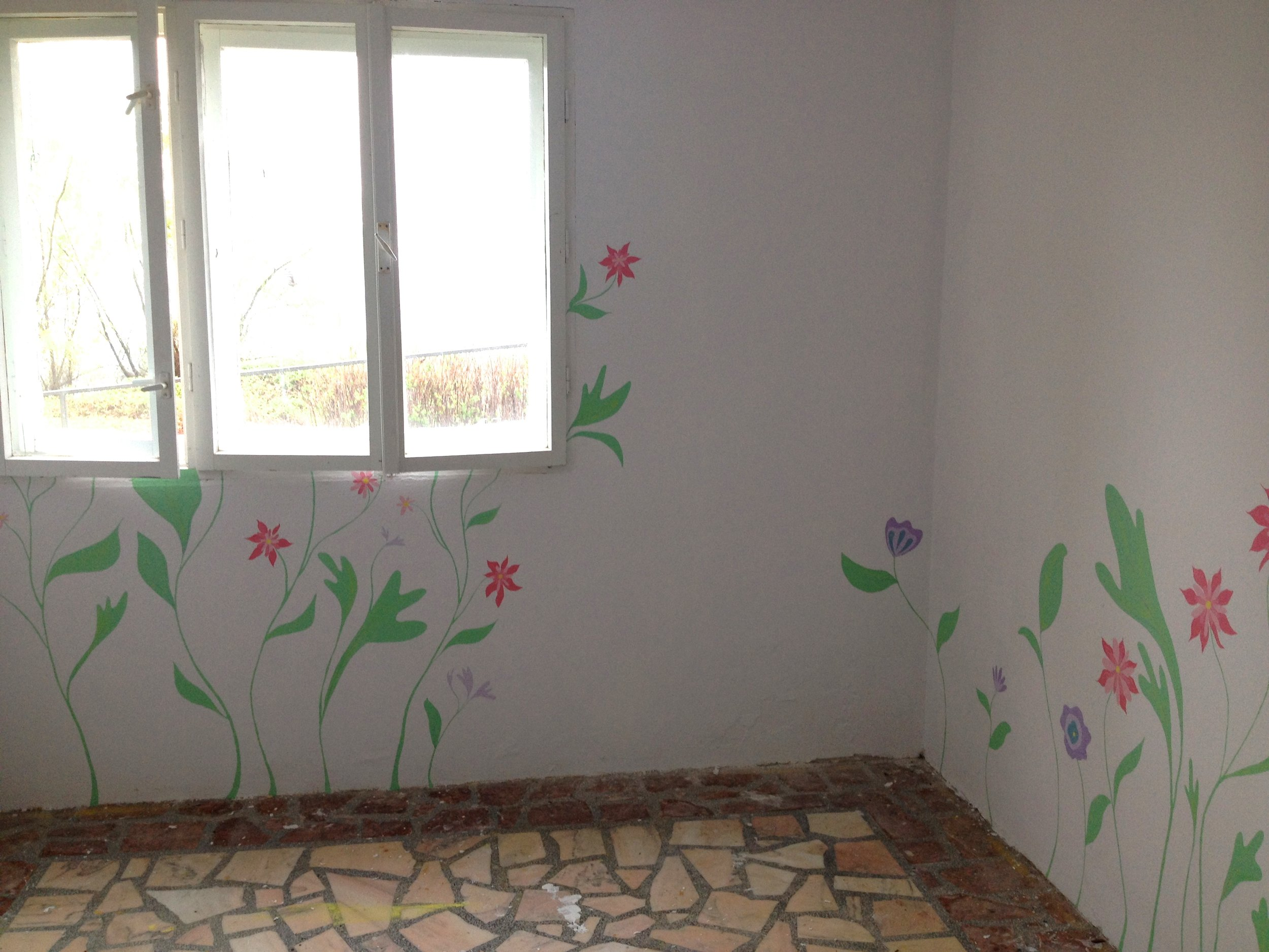 painting a garden mural in the prayer room at Casa Harilui, a retreat home for disabled children in Romania