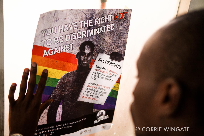 Receptionist Kelly Njoka puts up anti homophobic posters around ISHTAR Wellness center, Nairobi, Kenya