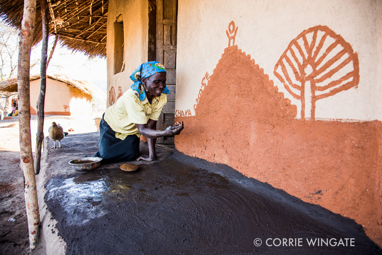 An elderly lady paints her house, rural scene, Kalonga village, Salima distict, Malawi