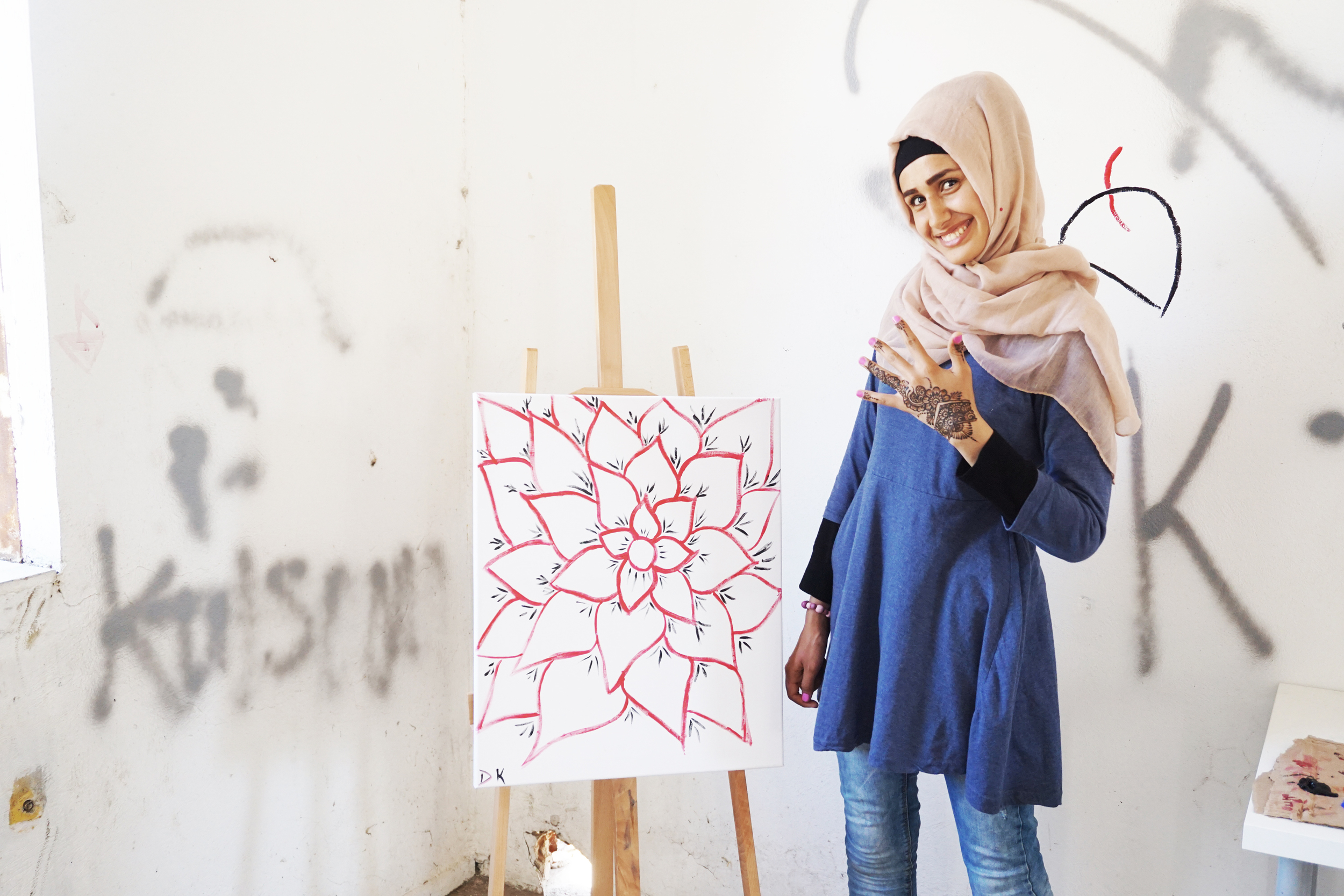 Young girl proudly displaying her art in the Art Space