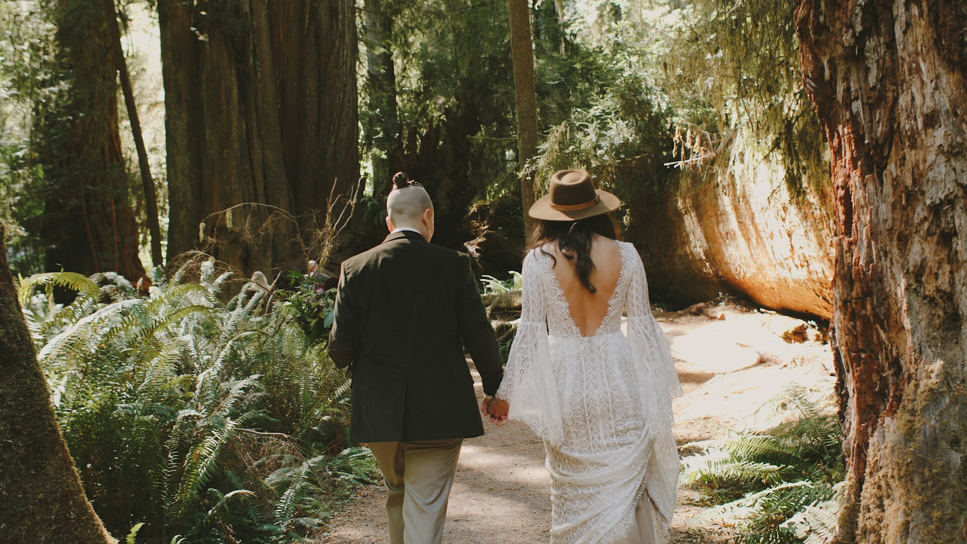 Couple walking through the redwoods after their wedding under the trees. They are holding hands and facing away from the camera.