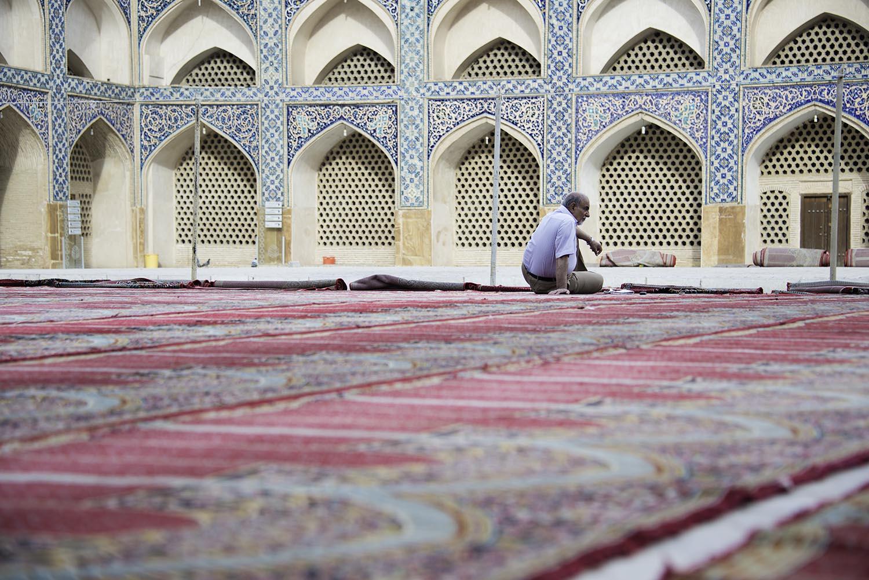 Man Sitting on Prayer Rugs