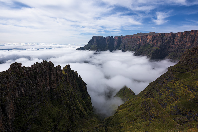 A beautiful autumn morning high up in the Drakensberg mountains. Inversion below, high clouds above and dappled sunlight hitting the dramatic landscape as seen from the view point near the Witches peaks. The Eastern Buttress, Devils Tooth and the Toothpick can be seen at the end of the Amphitheatre wall in the distance.