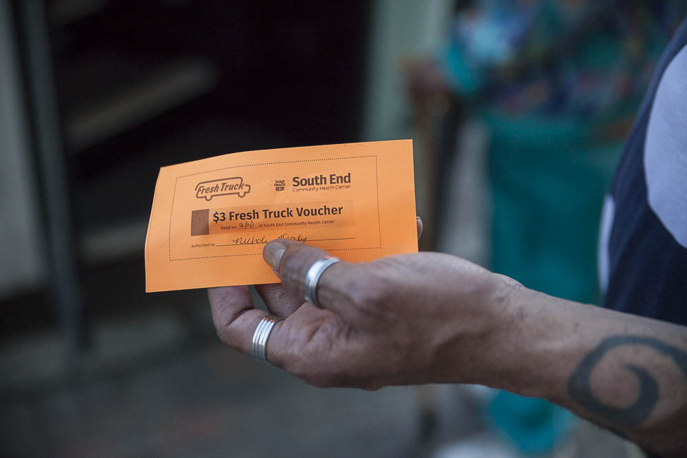 A patient of the South End Community Health Center picks up his voucher before shopping at the Fresh Truck. Through Fresh Truck's Food Rx program, health centers around Boston provide their patients with Fresh Truck vouchers to help them buy healthy food.