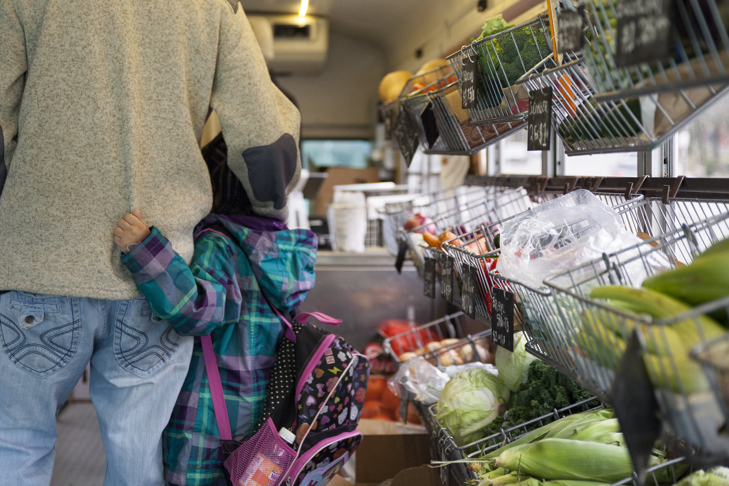 A father and daughter pick up weekly groceries at the Fresh Truck Market near Franklin Field in Dorchester.