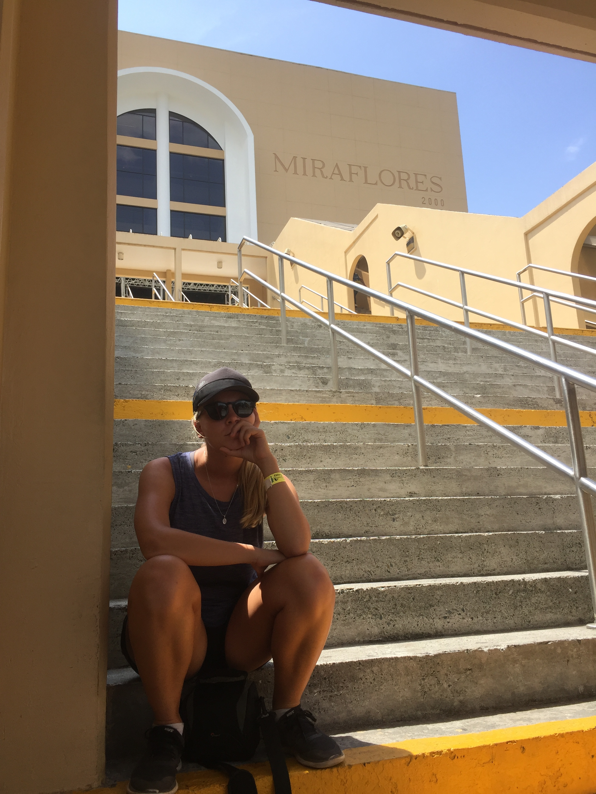 Danielle on the stairs of the Panama Canal's visitor centre waiting for the next Hop-on Hop-off tour bus.