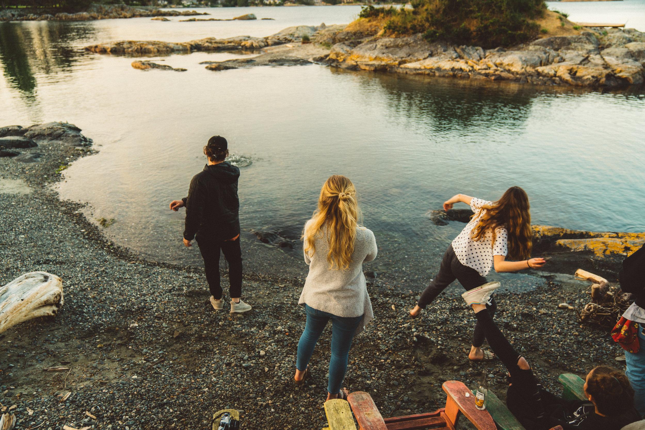 Jack and Annika skipping stones while Tay, Marijke, and Niko look on.