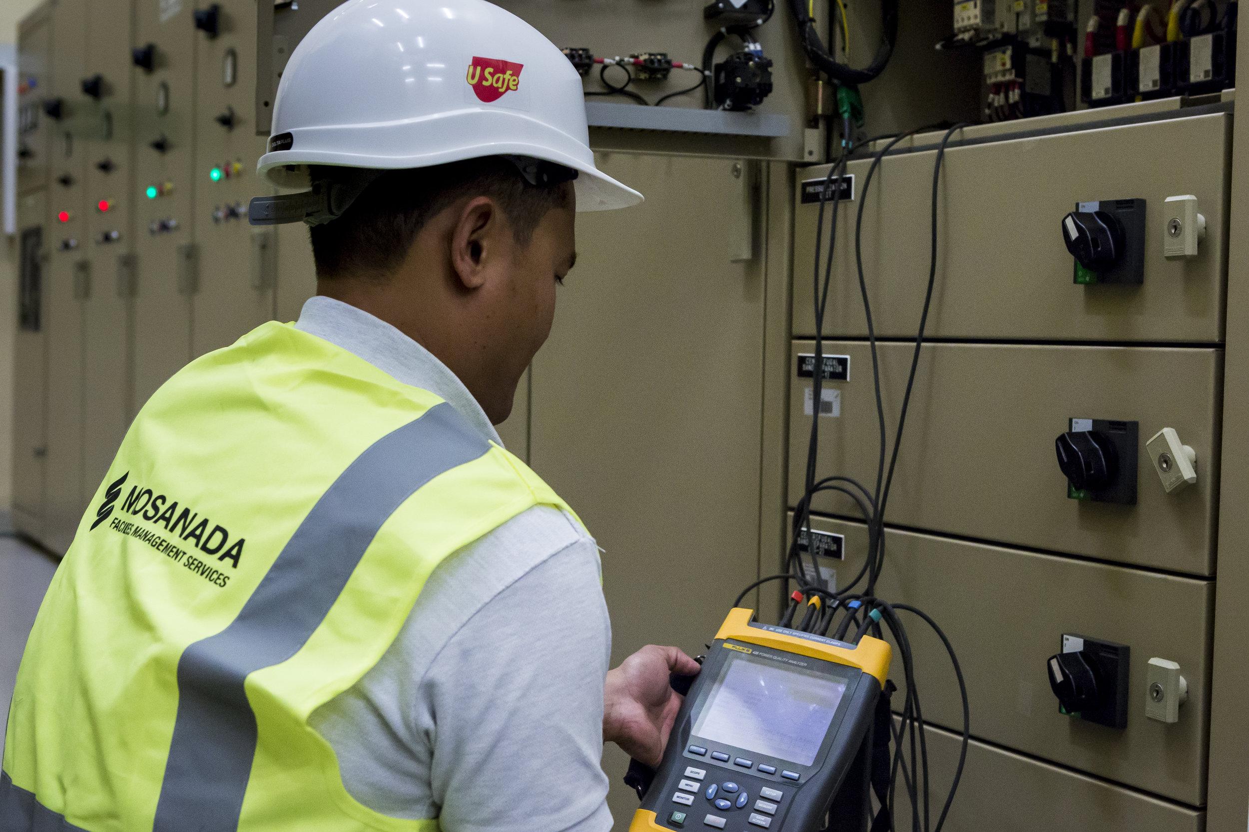 أحد مهندسي مساندة و هو يستخدم آلة تحليل الطاقة لجمع البيانات خلال التدقيق و مراجعة الطاقة