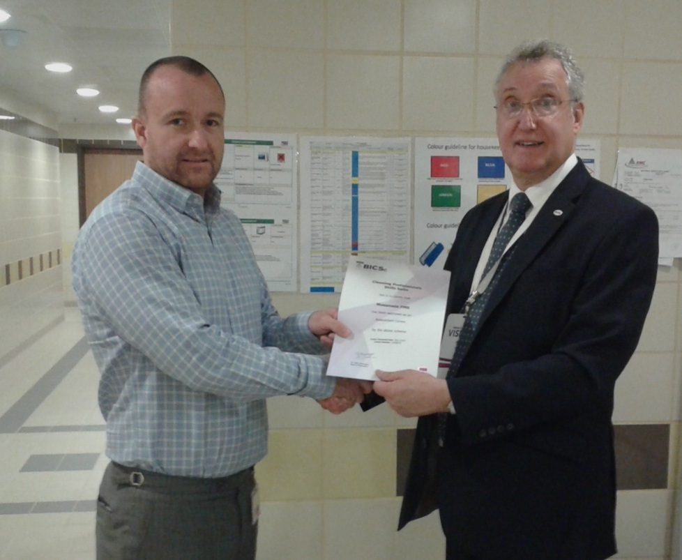 Chris Thomson, Senior Manager - Housekeeping (left) accepts the accreditation from BICSc.