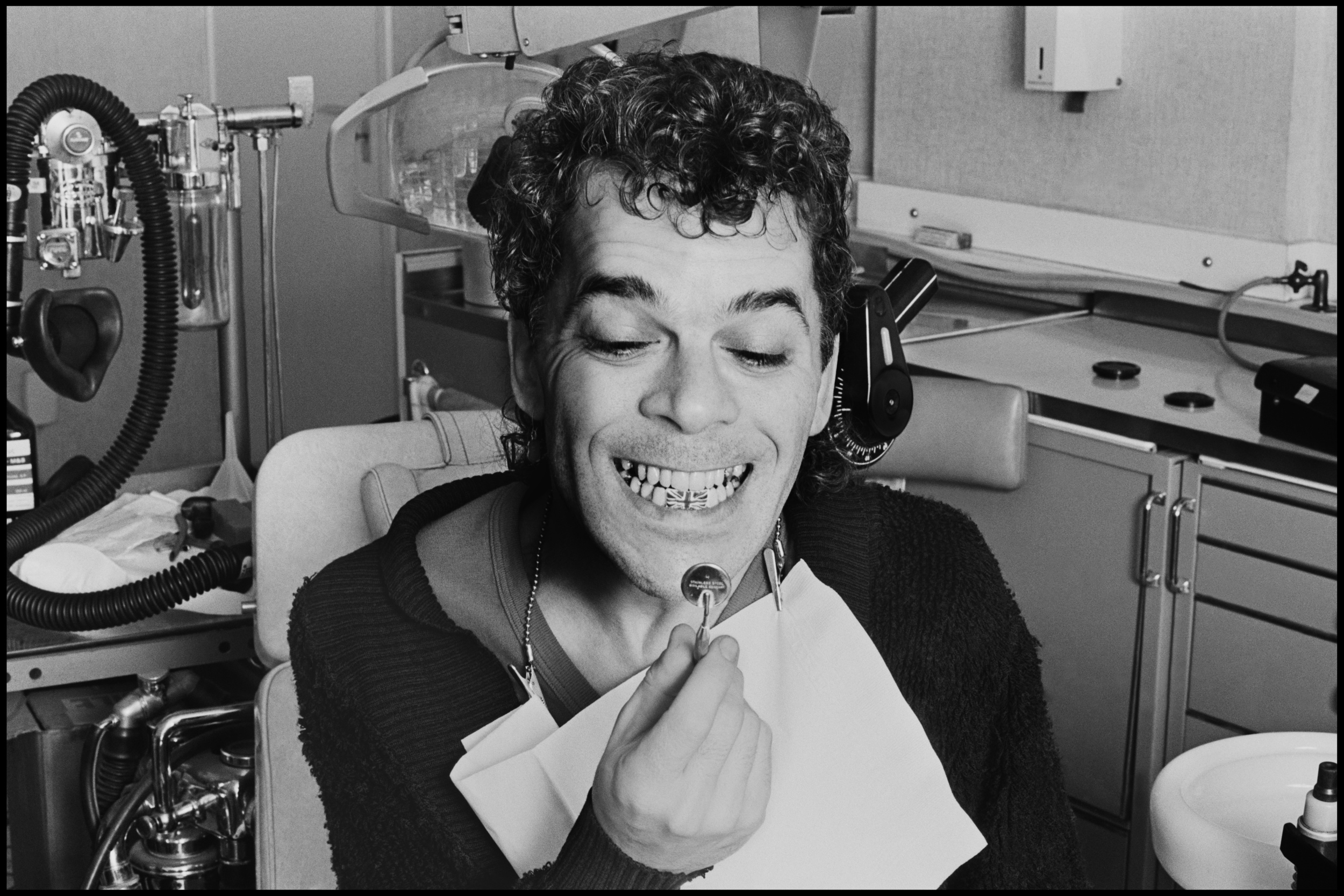 Ian Dury at the Dentist 1978  Whilst others had problems with him, I always found Ian Dury to be fun to photograph and his enthusiasm made the job easy, no matter what else might have been happening he always switched into photo mode for me and we did some memorable shoots together.  In 1978 the Stiff Tour had made Ian pretty successful, the first album had sold really well and his management set their sights on America.  But before he went there, and paid for by the royalties from Hit Me With Your Rhythm Stick, he decided to get his teeth fixed. Like fellow Punks, Lydon and Strummer, Ian's teeth were in terrible condition and he underwent serious dental work.  Due to the pressure of gigging he had this done in stages and the Dentist dealt with his lower jaw first, this involved putting a temporary bridge in place and while chatting to the Dentist Ian came up with a unique idea, just in time for his first trip to the Americas.  He had a Union Jack painted on this bridge so that when he gave those septics (septic tank = yank) a big toothy grin they would see the flag of his beloved Britain.  Hearing about this it seemed a natural thing to take photos of, and so I went down to Harley Street with my lights and set up in the Dentist's office. Ian sat in the chair and mugged away for the camera, it's one of my favourite sets of photos of him and the NME liked it enough to use it as a cover.
