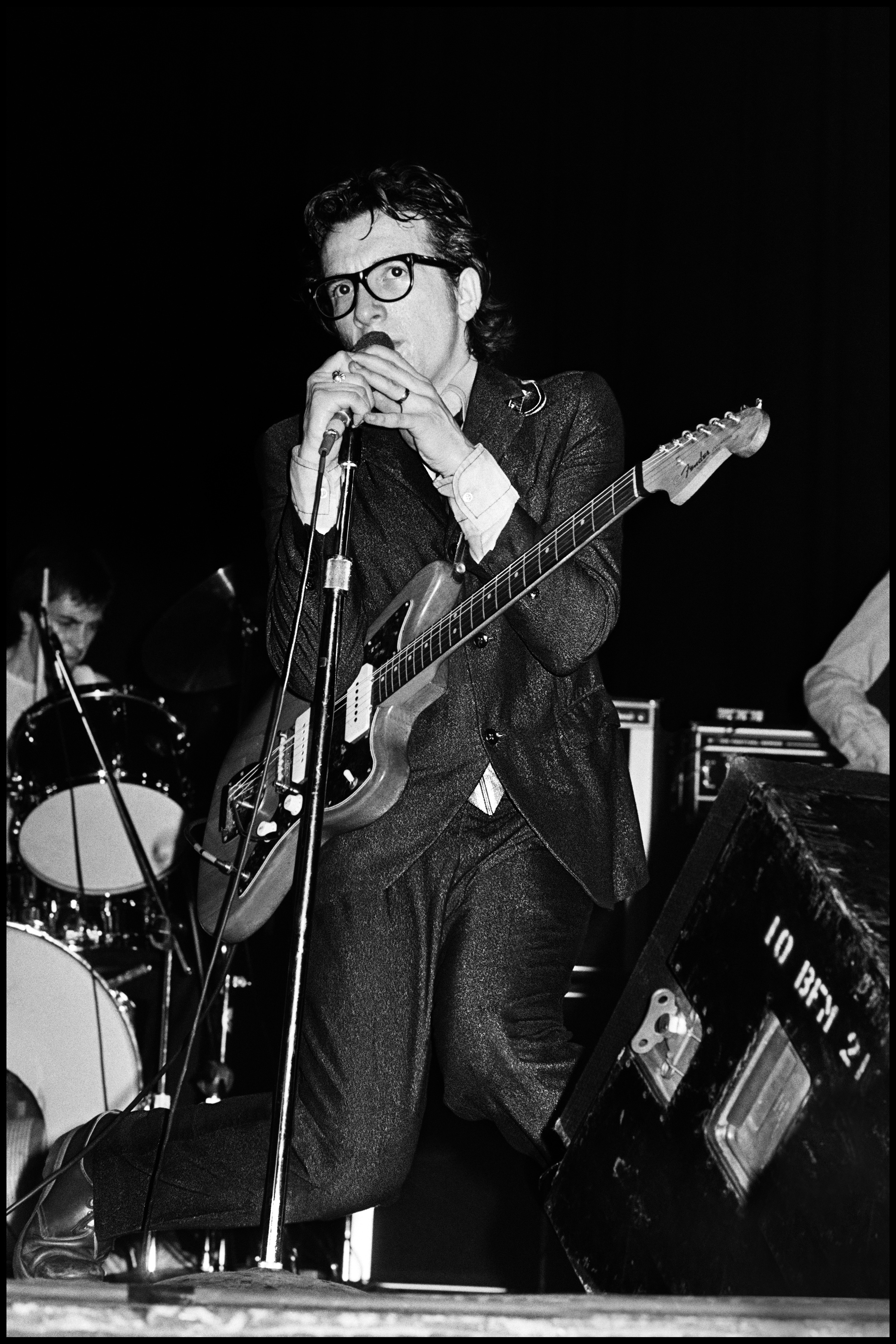 "Elvis Costello at The El Mocambo - Toronto 1978  My philosophy regarding live photography was simple, instead of wasting film, study the show on the first night, see where the best opportunities occur, then concentrate on getting the best photographs during those numbers the following night.  Given that Elvis was playing the El Mocambo, a small club in Toronto,it meant using flash, and that meant taking as few pictures as possible.  I saw that during Less than Zero and Watching the Detectives EC gave his most animated and manic performances. Not only that, he dropped to his knees in Detectives just after singing ""she's painting her nails as they're dragging the lake"" and my aim was true, it was to catch that particular moment.  I waited patiently and caught him right on cue, I was mighty happy with myself, but his manager was not happy with me.  Whilst accepting that Elvis did this every night Jake did not want the public to know, he wanted each audience to think it was spontaneous, so he told me quite bluntly that I could not use the photo.  I reluctantly agreed, because I could see the logic behind this decision, it was strategic in nature and I respected that. Jake respected me for agreeing and from that day on gave me total access to EC whenever I needed it.  So I waited thirty five years before making it available, to me it sums up those early years perfectly."