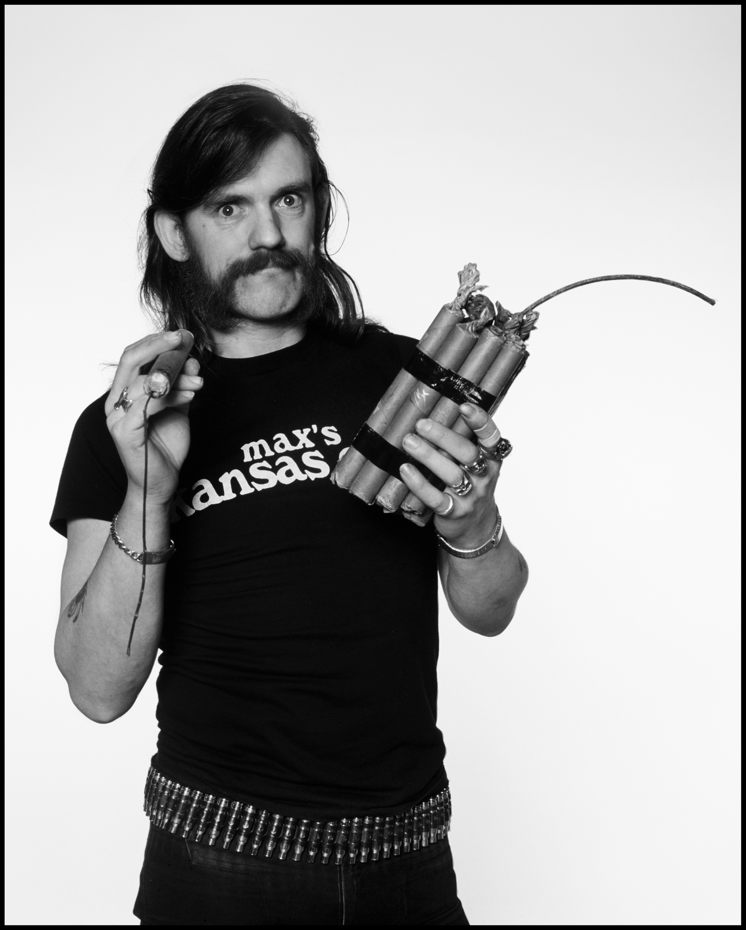 Lemmy - London 1984  I think I first came across Lemmy in 1971 when he was in Hawkwind, he was someone you often saw in Ladbroke Grove or at the Marquee and other watering holes around town, as he was best mates with Mick Farren he became a regular visitor to the NME offices in '75 and '76 before he formed Motörhead.  In fact I reviewed Motörhead's first gig at the Marquee in 1977 for the NME and whilst I saw potential in the Uriah Heep/Black Sabbath area I would never have thought they would have been as successful as they became, let alone expect that they would still be going strong thirty five years later.  Lemmy is a gruff, slightly imposing, yet adorable kind of a Rock Star, quite malleable too, always happy to oblige when one needs a quick photo for a Magazine.  This picture was originally shot for the cover of Time Out in 1984 and the 'session' lasted about ten minutes. Lemmy arrived, took off his leather jacket, grabbed the fake dynamite and stepped into the studio grinning. He then did 24 assorted poses, giving me everything I needed on exactly two rolls of film.  Knowing that all good photographers were skilled in the art of quick shoots, he put the dynamite down, put his leather jacket back on and left the building.