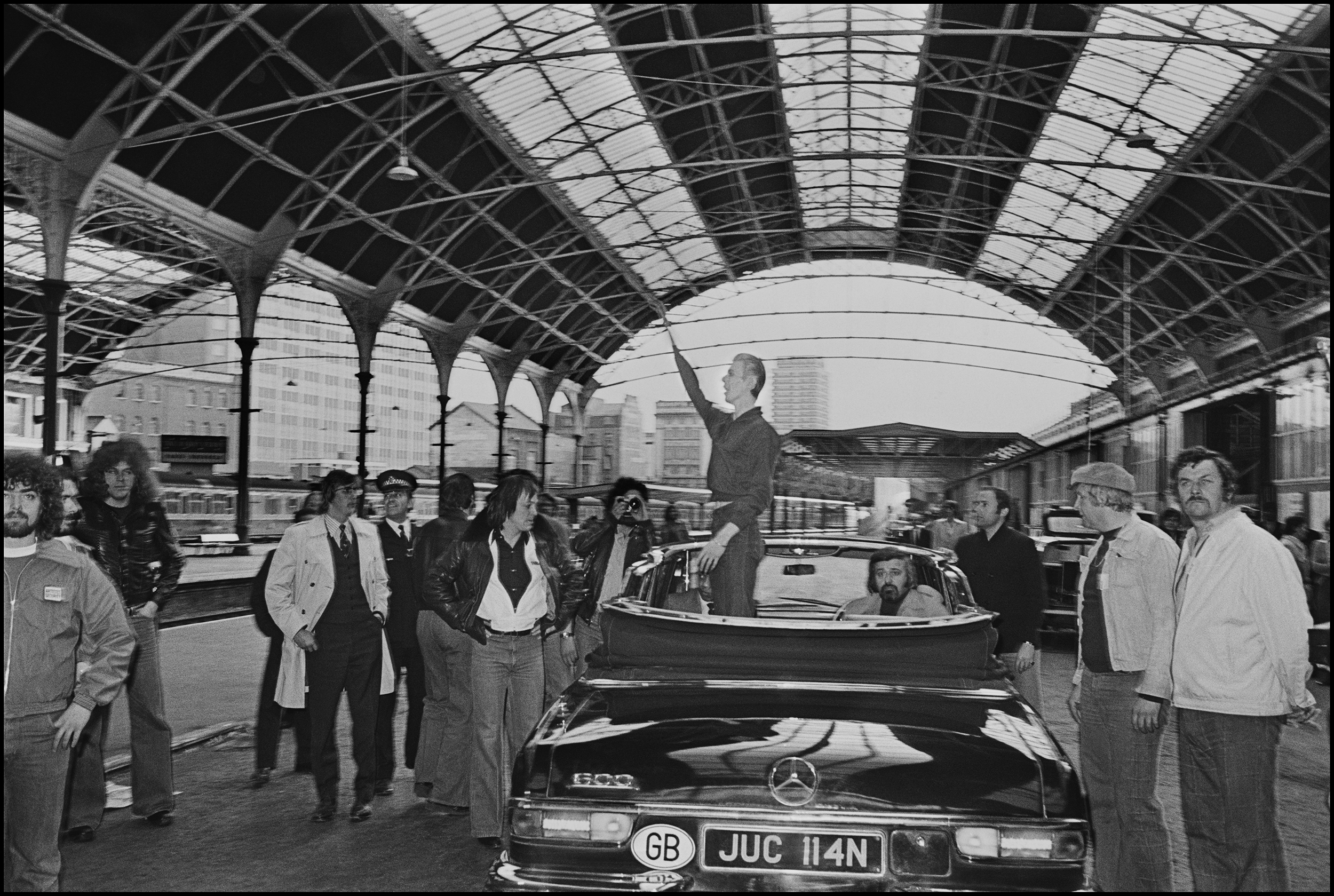 David Bowie - Victoria Station 1976  This photo became the centerpiece of what came to be known as 'The Victoria Station Incident'.  David Bowie hates flying, so when he returned to the UK for some concerts as the Thin White Duke in 1976 he arrived by a special train. It pulled into Victoria Station in the middle of a quiet Sunday afternoon, that's if you call a bunch of girls screaming at the top of their lungs quiet.  He walked a few yards from the train carriage to a waiting open topped BMW which then whisked him to another platform where the car reversed towards the hordes of screaming girls. It stopped near us photographers, David stood up in the back of the car and waved to the crowd, then, he drove of to an undisclosed location.  Unfortunately because of the gloomy late afternoon light at Victoria Station I used fill in flash on the four or five frames I managed to rattle off before he split.  When I showed the image to the NME the following day they decided to enhance his left arm by drawing a hand on the image, because of the flash it was partly missing. But when we saw the paper on Wednesday it looked very much like he was giving a Nazi salute.  The press picked up on this and put it together with some quotes on fascism he had made in Europe and lo and behold David was vilified as a Nazi. I feared it might harm our relationship but he shrugged it off saying it wasn't my fault, that I'd just caught a wrong moment and that he was indeed waving at the crowd. Nobody believed him of course and the Victoria Station Incident became part of a Bowie folklore.