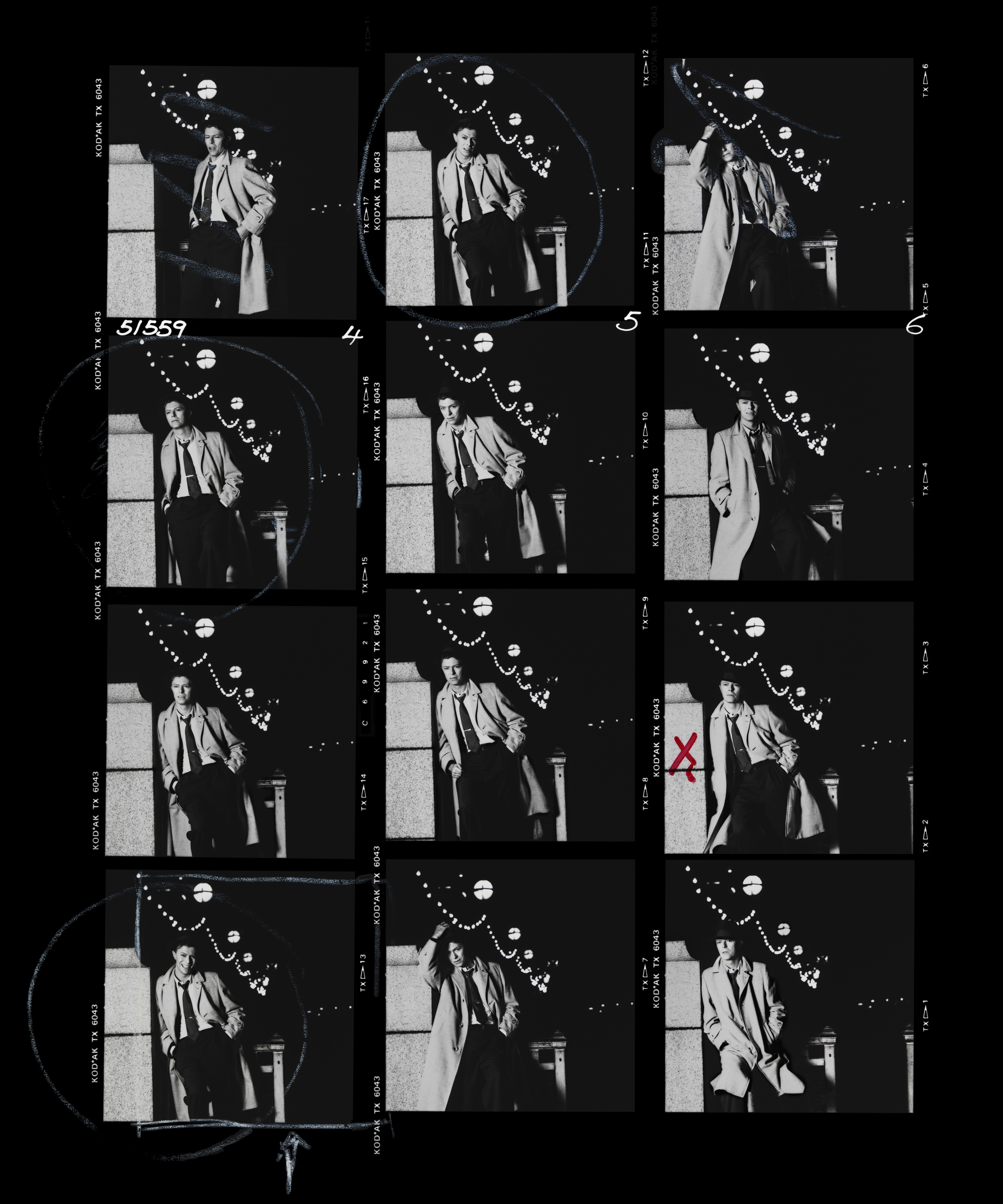 Absolute Beginners Contact Sheet 1986  David Bowie is one if the easiest people to work with, he's so good in front of the camera that you can do a record cover in a single roll of film. When you are on a film shoot nothing endears you to the Director more than the ability to shoot fast.  Everything was pre-lit and tested beforehand, all it needed was for David to step into the frame and pose for three minutes.  Contact sheets can tell you a lot about both photographer and sitter, the twelve frames on a roll is now a thing of the past but back then it was the order of the day.  When you have to hand over the sheets to the publicist you never know what you will get back from the artist, sometimes with Rock Stars only a single frame from a dozen rolls is marked, sometimes they approve three or four, but that is not the case here.  In the right hand strip you can see a small X, this was the choice of David's management, safe as houses, but also kind of boring.  On the whole page you can see exactly the way David marked it up, excluding only two frames as a bad photo, ignoring seven more frames as they were OK but not great.  Then he has circled three of the frames including 4C, the one where he is smiling. The Art Director then marked a square around that same photo. I was very happy David and the AD chose it, but this surprised everyone who worked for him as he has never, before or since, smiled on a record cover.