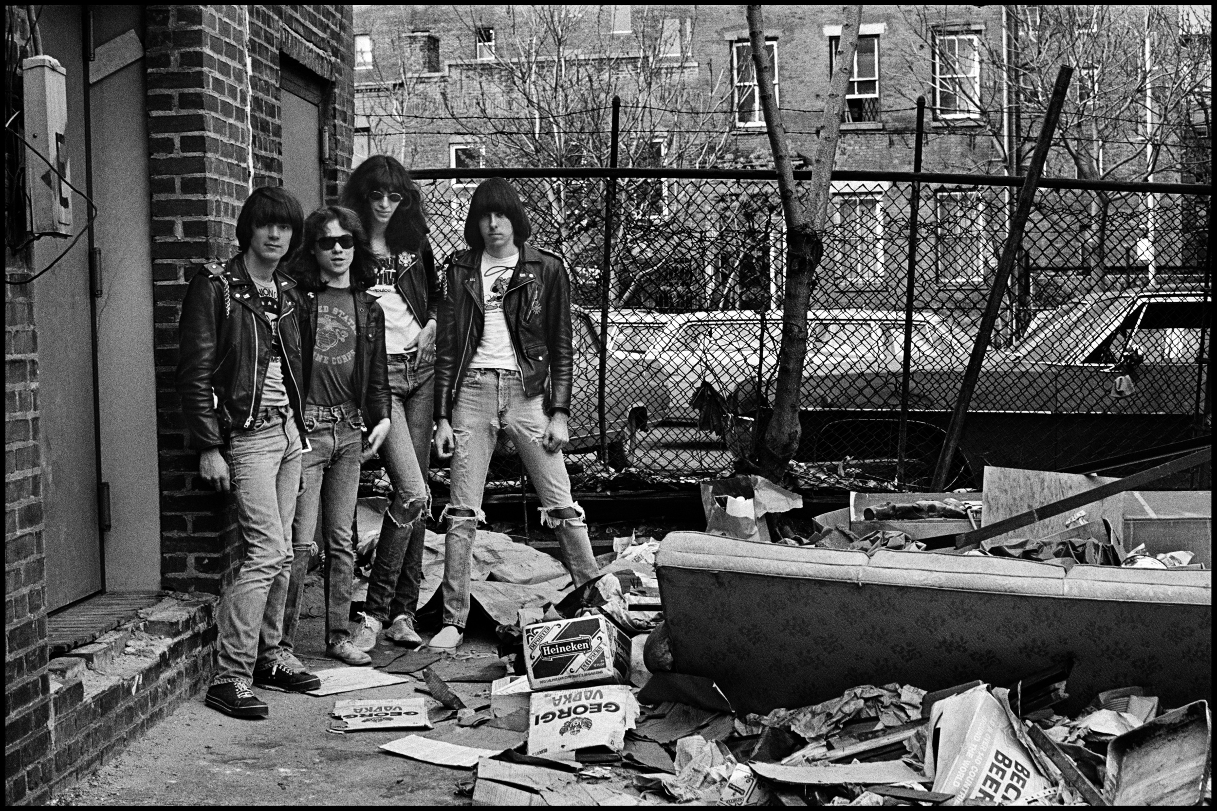The Ramones - New York 1977  In April 1977 Mick Farren and I came to New York to check out the punk scene for the NME. We went to all the well known Clubs including CBGB's, Max's Kansas City, the Bottom Line, Danceteria and the Mudd Club.  Joey Ramone lived close to CBGB'S which was on the Bowery in the Lower East Side of Manhattan. Initially we took photos on the roof of Joey's apartment building but although it looked like New York it did not really have the right feel.  I had spotted this alley when walking over to Joey's place, it was a block from  the Bowery and seemed perfect to me, it was full of trash and totally run down, back then huge parts of Manhattan were like this, the money had run out and the city was bankrupt.  I dragged the four Ramones to the location, I did a number of group shots, aided by their Artistic Director the late Arturo Vega. It seemed odd having somebody else telling the band what to do, all they did was stand there in a line, but it made them relaxed so I was happy to let him help.  To me this sums up the American Punk scene at that time, leather jackets, t shirts and jeans was the look they all had, it's a shame the Ramones never had the true success they deserved, but their influence should never be underestimated.