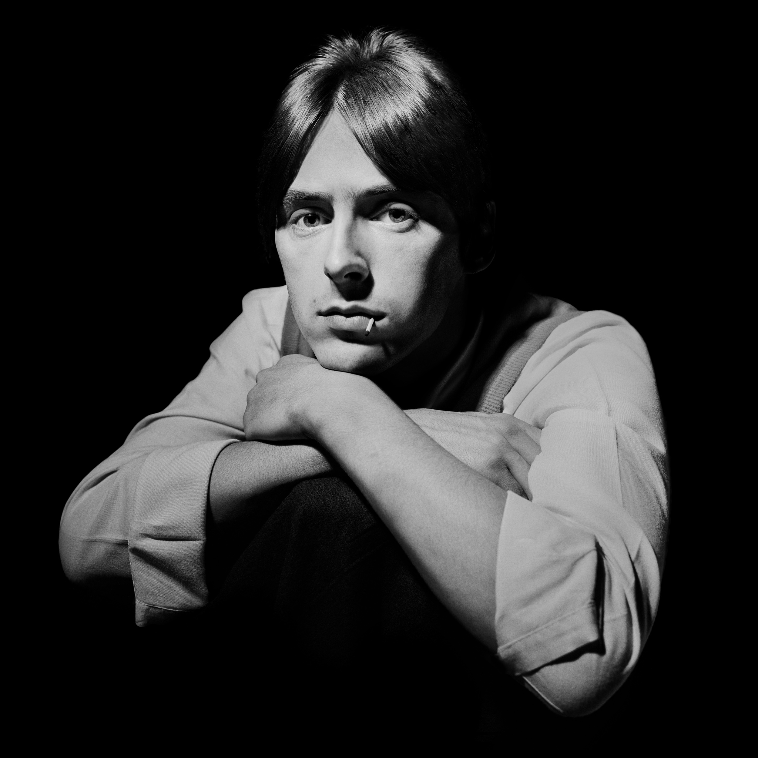 Paul Weller - The Face 1981  Whilst Terry Hall never appeared to smile, he was certainly not miserable, he just saw no need to smile, if you asked him to he did, albeit in a very minimalist fashion. The same was not true of Paul Weller.  I remember this shoot well, it was a cover story for the Face, he was wearing a bright red vest, a clean white shirt, and his hair was a perfect copy of Stevie Marriott. You could certainly direct Paul, it did not do you much good however. All you got was the look, a stare that questioned his reason for being there, that this was part of the job, that you would never see below the surface.  Being for the cover it needed to be good, I tried everything to get some kind of look on his face, every angle failed, nothing brought a smile to his face, nothing I said caused any change in him, the photo needed something and I told him so.  Out of his pocket he produced a box of matches, he put one in his mouth and the picture somehow now had a life, he moved it around slightly between frames, as if it were an important prop. His face is exactly the same in all the pictures, the position of the match governs the choice, yet somehow there is something here, a flicker of interest in his eyes, but you have to look really hard to see past the persona he has always projected, that of Paul Weller, leader of the Jam, leader of the Style Council, and now the Godfather of Pop, I'm amazed he has lasted this long.