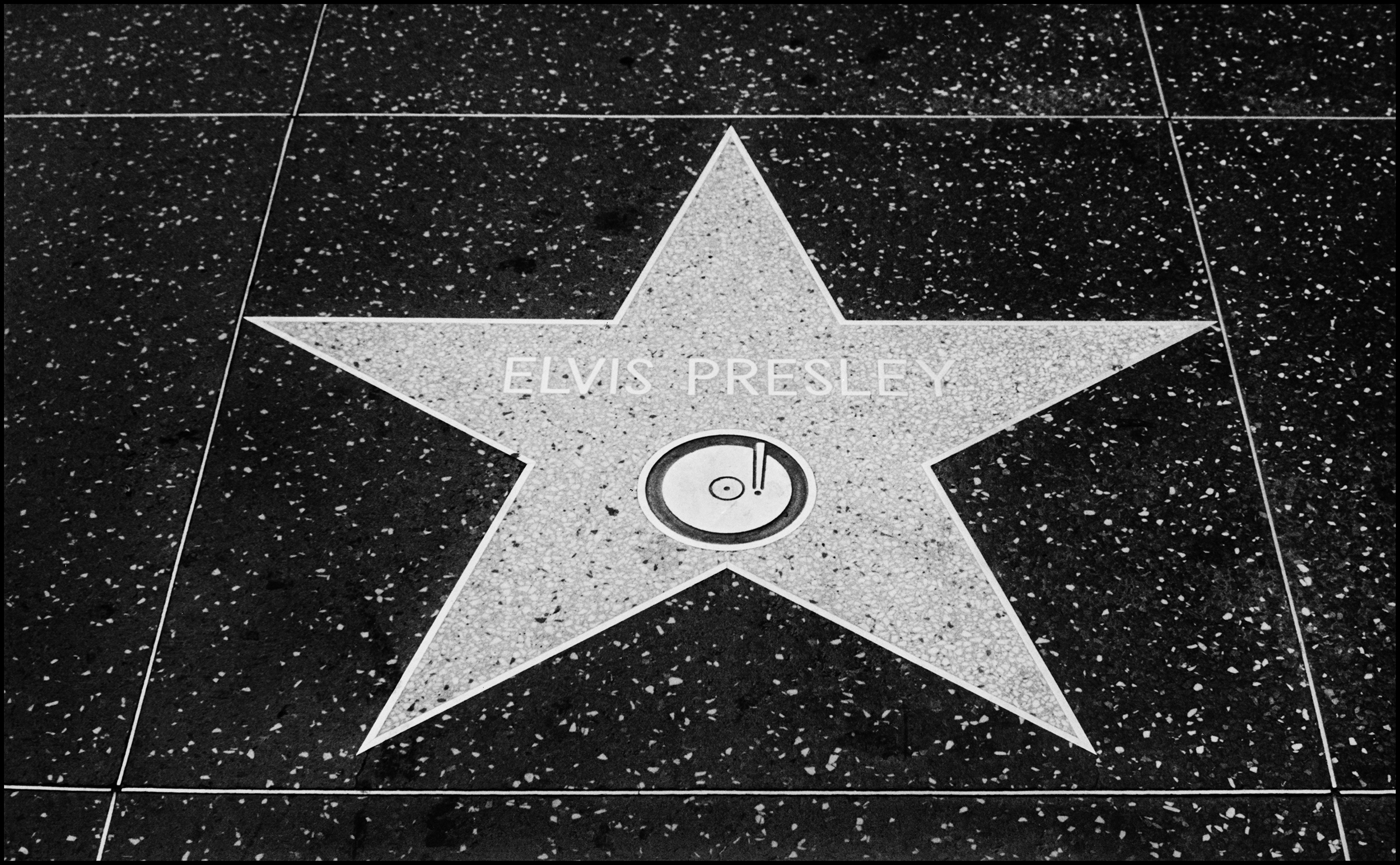 Elvis Presley's Star on Hollywood Blvd 1977  When this photo was taken in 1977 the US had just produced a worldwide phenomena, Star Wars, and I was in Los Angeles on the Thin Lizzy and Graham Parker Tour.  I had seen Star Wars at a press screening in London earlier in the year, but, the chance to see it at the famed Gauman's Chinese Theatre in Hollywood was a something I was not going to miss. With a gig to go to in the evening I decided to attend the 12.00 showing, it had only just recently been released and the cinema was pretty full considering the time of day. Seeing Star Wars on this massive screen in such a legendary Theatre was a great experience, in fact I stayed for the next show and saw it a second time.  Afterwards I wandered off to a comic bookstore to seek out some Star Wars material, I did not realize that I was walking down the Hollywood Walk of Fame, back then it was exactly that, a long line of legendary Actors and Actresses, then, lo and behold, I was standing at Elvis Presley's Star. He was of course well past his prime at this point in his career, but that afternoon standing by his star had quite an effect on me. He may have had his career ruined by entering the Army, or more likely by making too many bad films, but you can't deny his ability as a stage performer.  The following year I was at a Ted Nugent Concert at Hammersmith Odeon, we heard the news that Elvis had died during the encore, I was going to visit with Phil Lynott after the gig and broke the news to him. Philip was deeply affected by hearing of Elvis's death, he went to his room and wrote King's Call.  The NME put him on the cover the following week, just a photo, no words, there was nothing you could say really, other than the King was Dead...