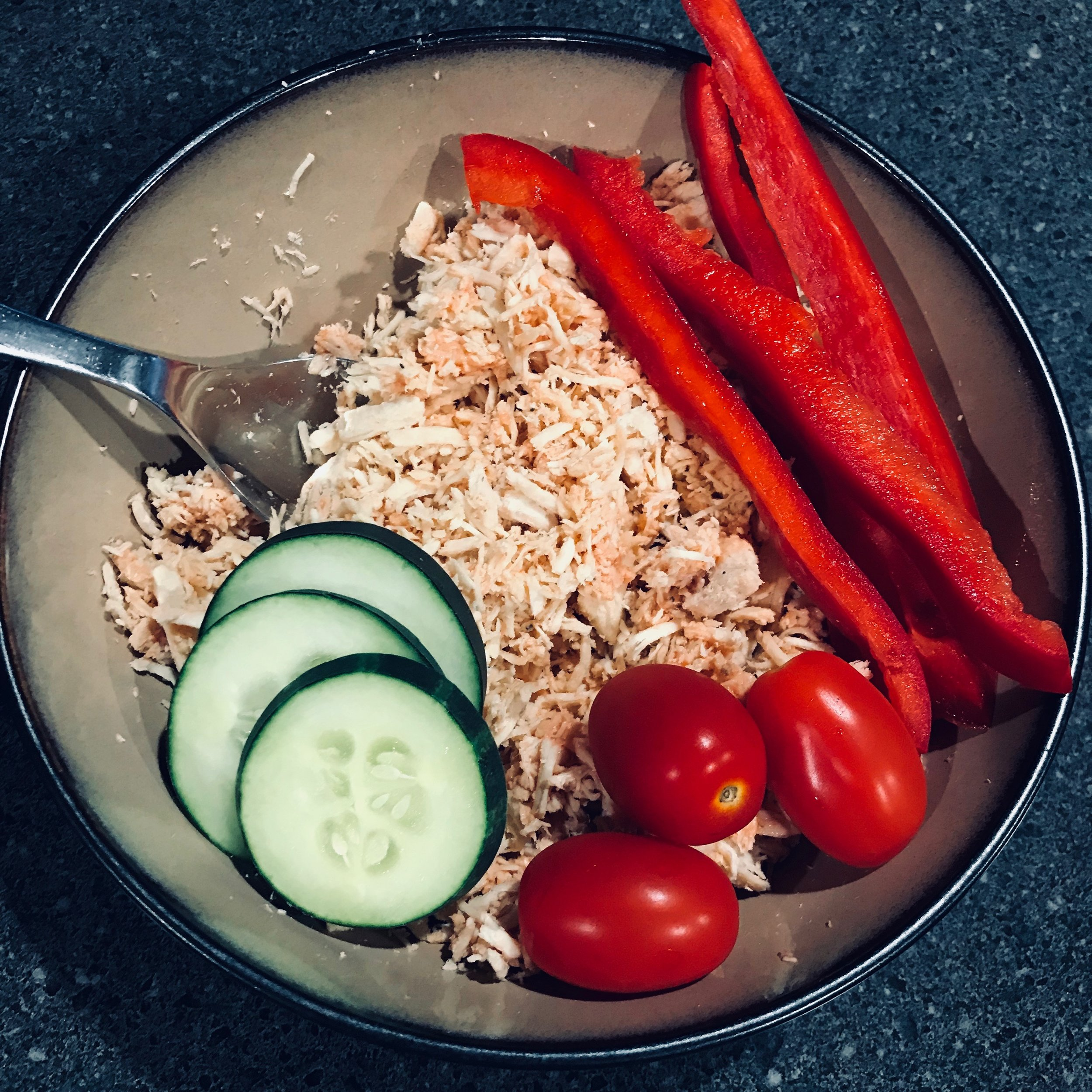 Shredded chicken + a few drops of Frank's Red Hot sauce, cherry tomatoes, red peppers, cucumbers.