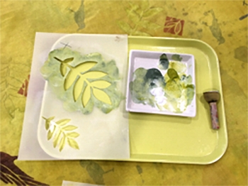 One of the stencils I used with a palette of paint and the stamping brush I prefer.