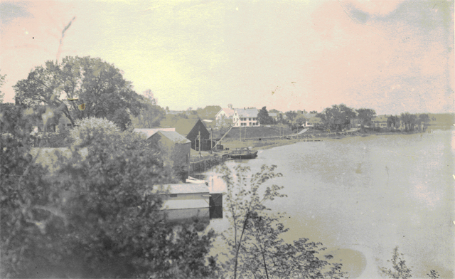 Squamscott River looking towards Fort Rock Farm, the Swasey Homestead, circa 1900. This photograph was taken prior to the construction of Swasey Parkway. The wharves and crane were vestiges of Exeter's days as an active port and shipbuilding town. Courtesy of the Exeter Historical Society.