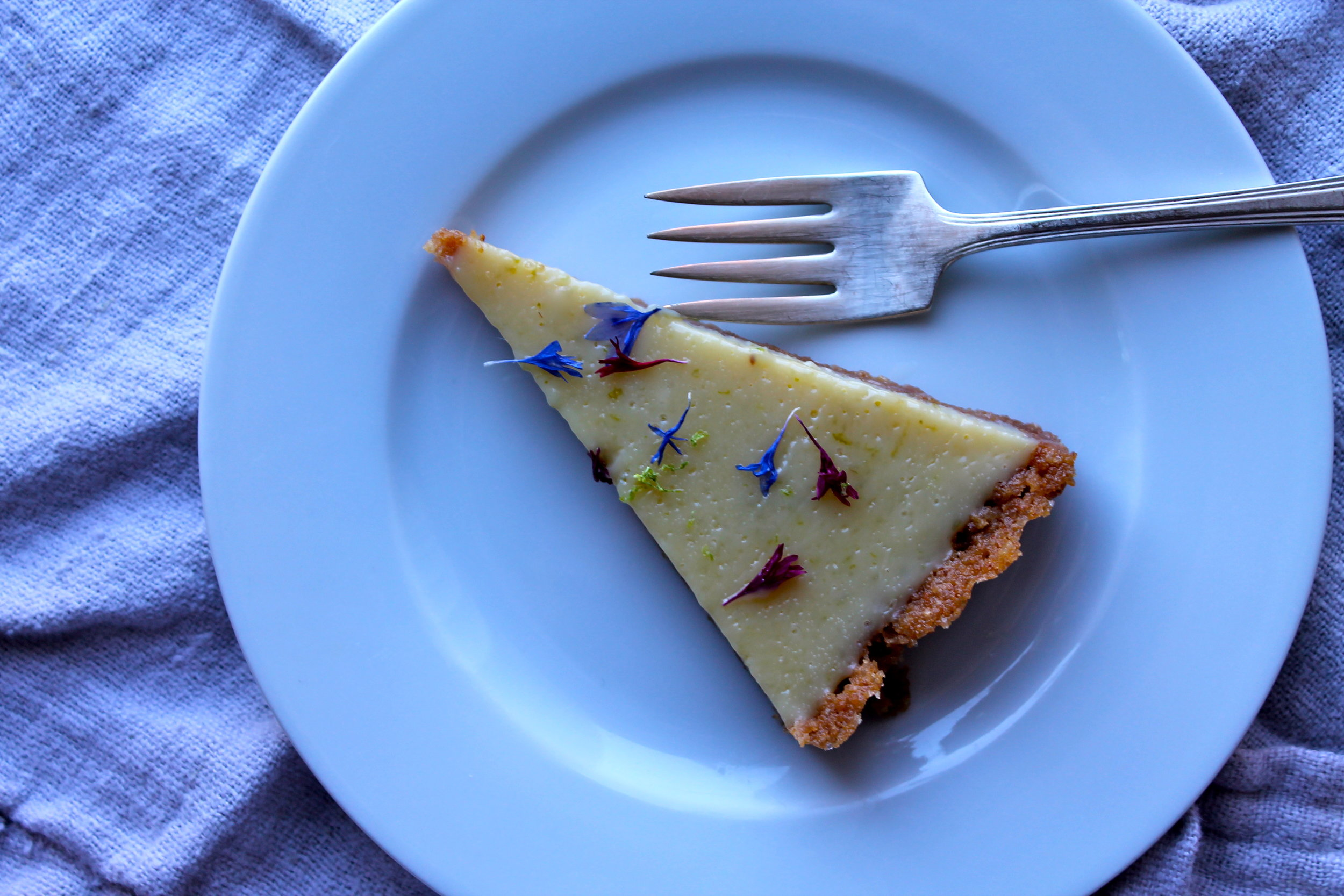 fresh lime tart with edible flowers slice