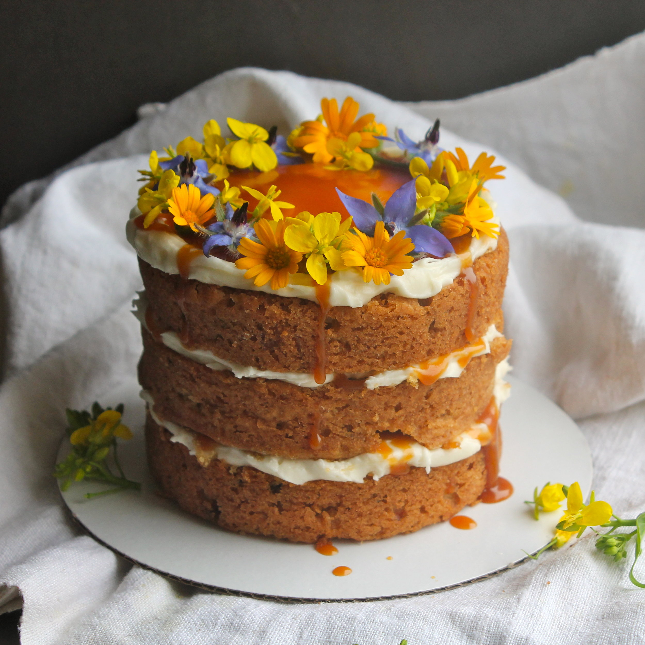 Edible Flower baby naked cake with salted caramel drips by Cake Bloom