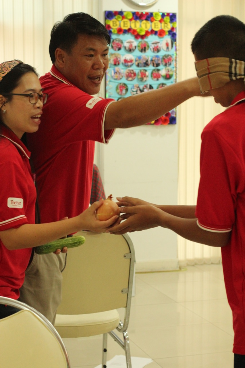 Family members work together with one member blindfolded to gather their ingredients.