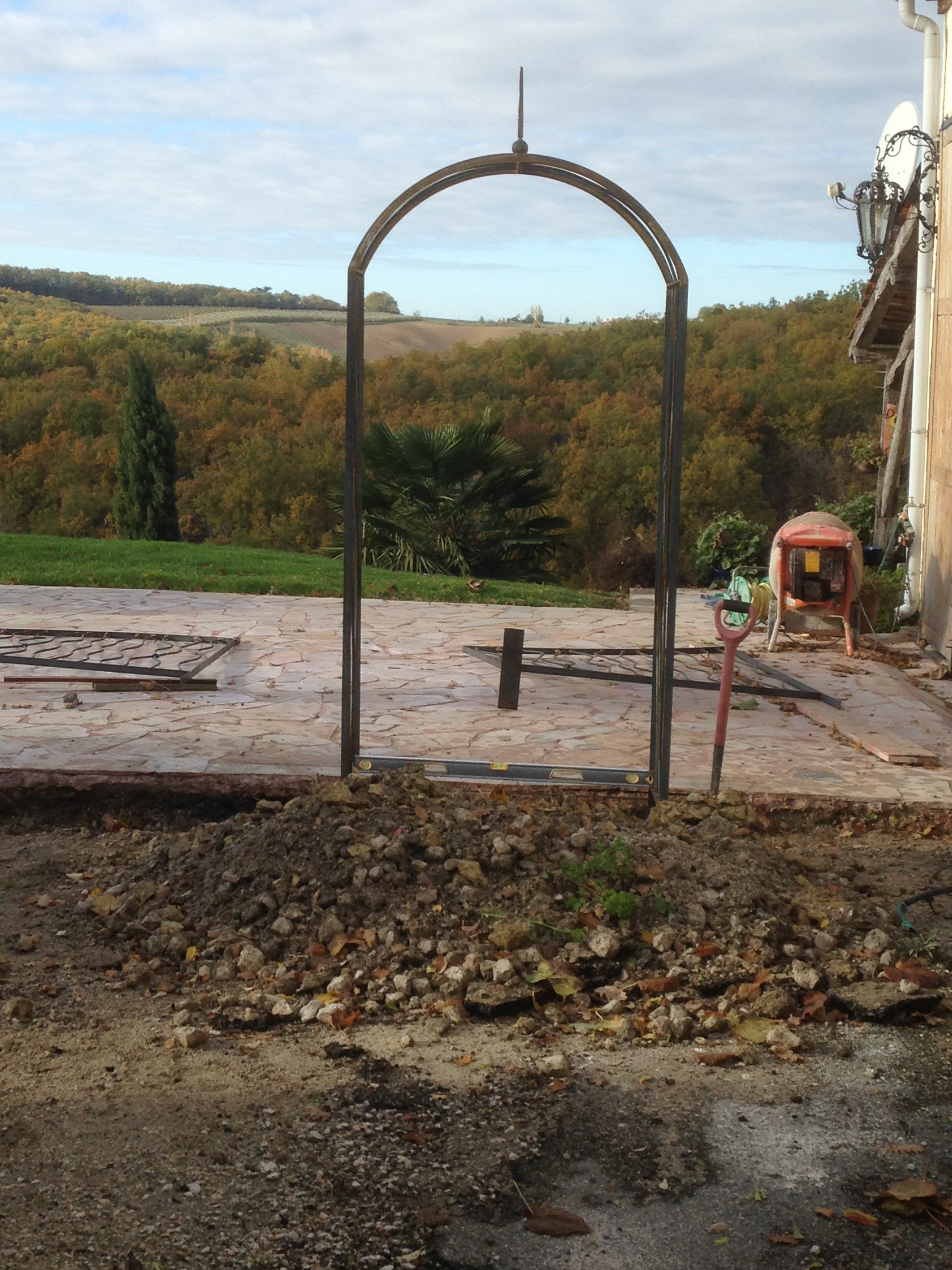 The arch is set in place first. It frames a lovely view over the rolling hills beyond. Note the necessary 'tools of the trade' on this worksite!