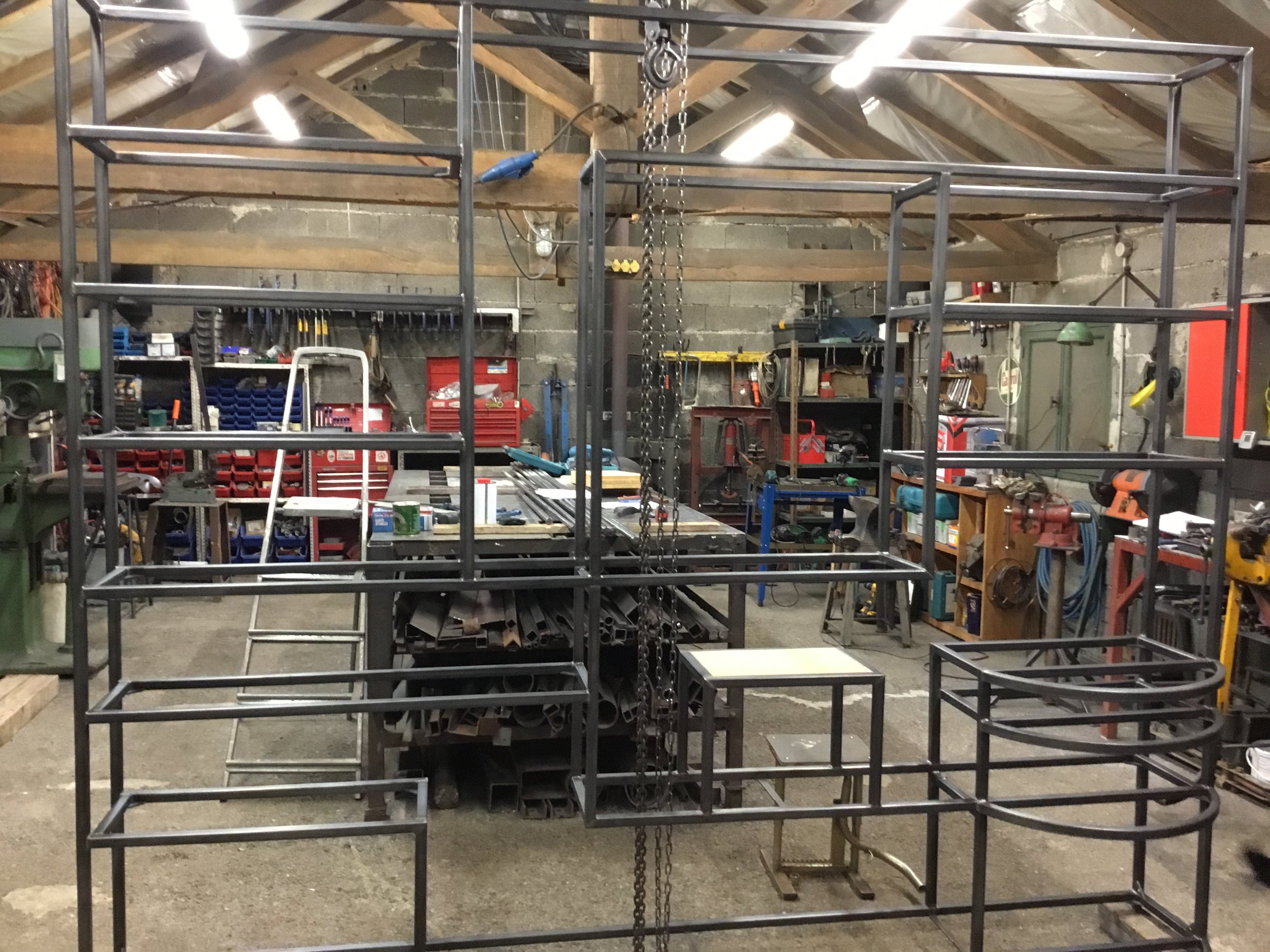 The 'bare bones' frame of the bibliothèque in the workshop. Wooden shelves were made to measure and then inserted into the frame once it was in place.