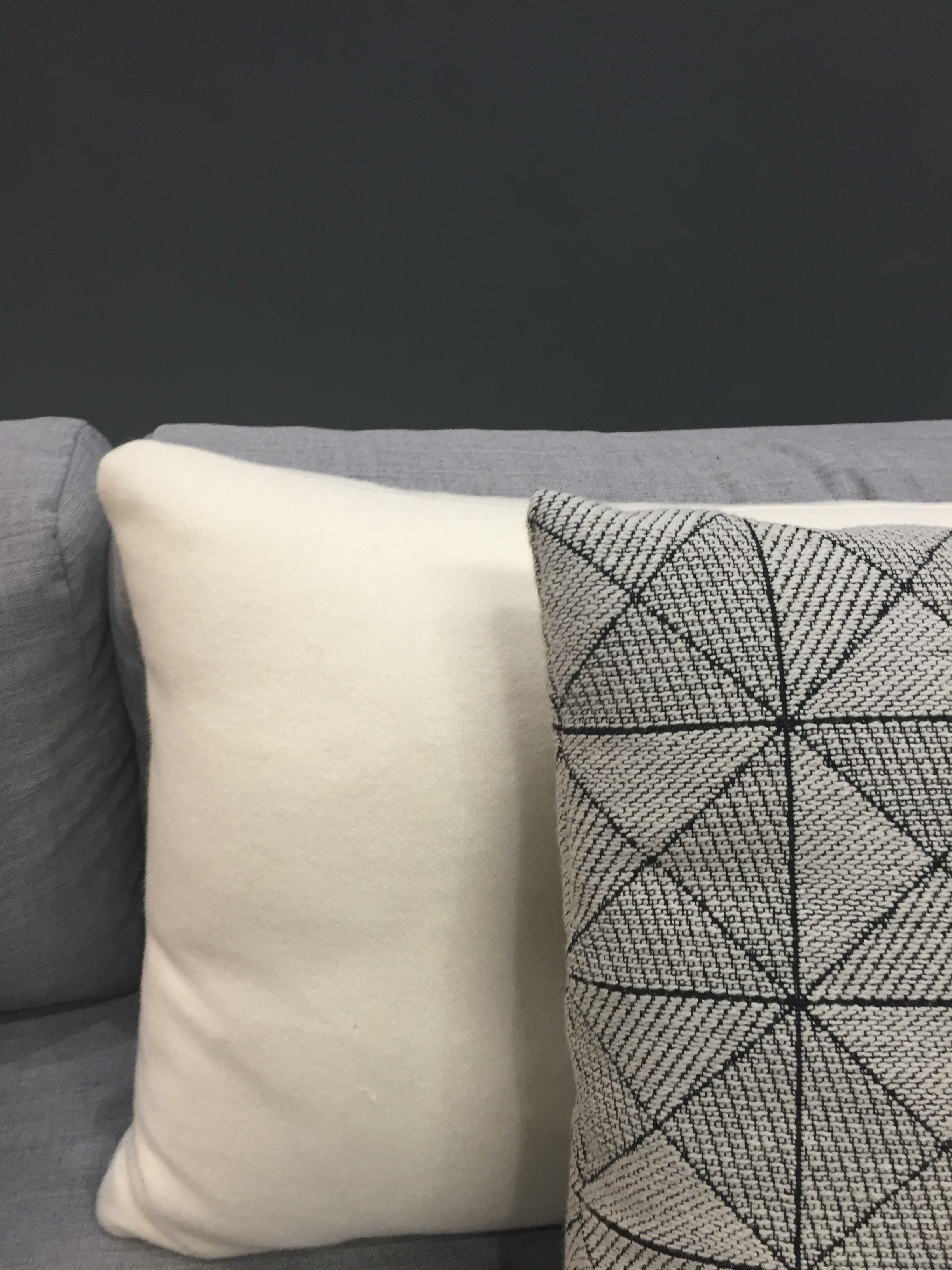 A close up of the Hay Dot cushion and Muuto Tile cushion.