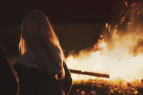 girl outdoors at night with a fire