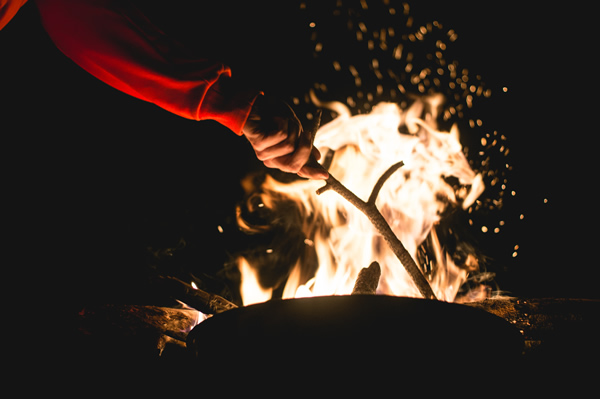 hand stoking a fire at night