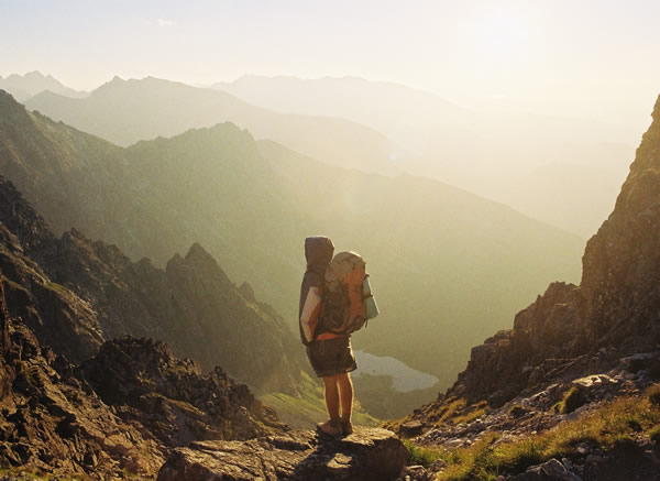 boy with backpack at top of mountain