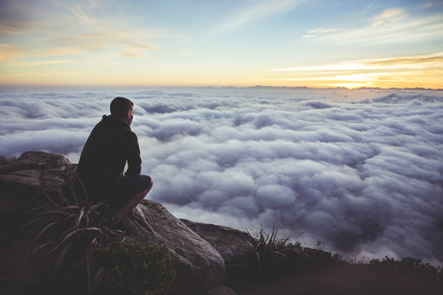 man on mountain overlooking clouds