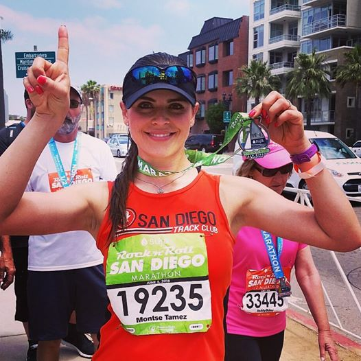 """SBMS client Montse Tamez, pictured above after completing the San Diego Rock 'n' Roll Marathon. Montse was previously trained by Coach Josh.  """"Coach Josh did an excellent job of preparing me physically, mentally, and logistically for my first half marathon. I had never run at this level before, and in a very short amount of time, he was able to prepare me by creating an easy-to-follow running plan. He responded to my questions and concerns with his own careful thought and expertise. I successfully completed my first half marathon and continued running from then on. Joshua is passionate about what he teaches, he very knowledgeable, and very supportive!"""" - Montse Tamez"""