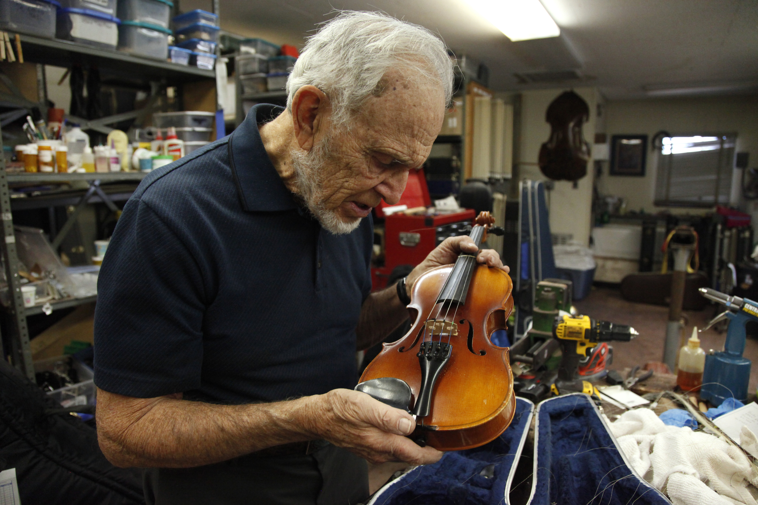 Ned Bloomfield inspects a violin in the Tucson Unified School District's instrument repair shop on December 17, 2015.