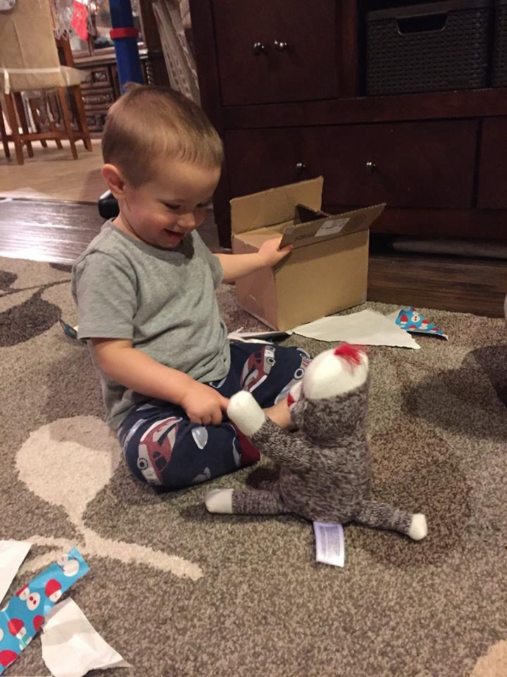 Opening his sock monkey from his Virginia family.