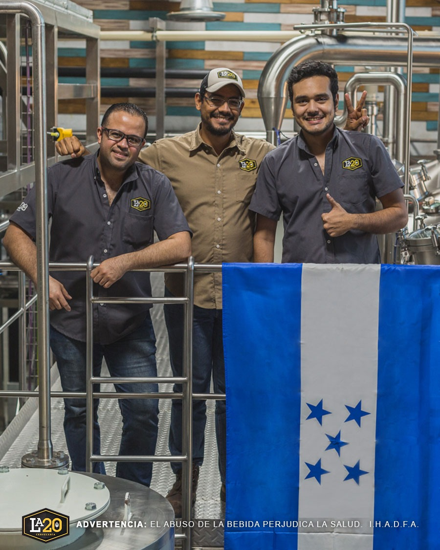 Hector (center) and fellow La20 staff standing proud in their new brewery.