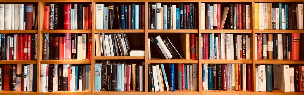 brown-wooden-shelfs-fully-packed-with-books-in-a-library-picture-id900301626.jpg