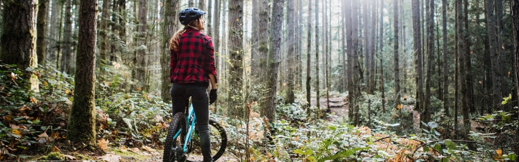 woman-mountain-biking-on-forest-trails-picture-id1077207188.jpg