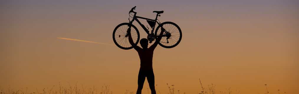 graphicstock-silhouette-of-mountain-biker-holding-his-bike-in-sunset-on-the-meadow_HAnvoln-W.png