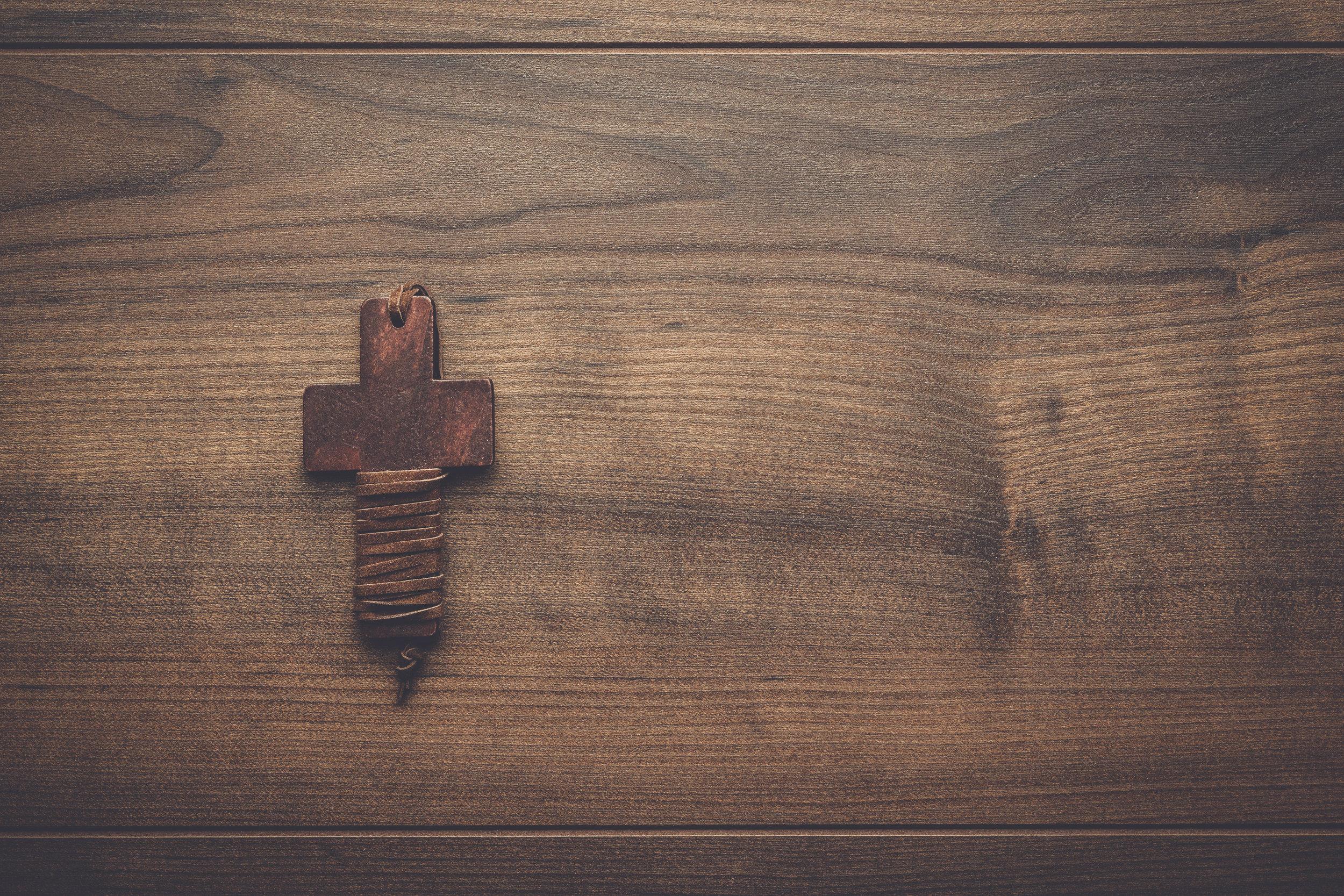 cross-over-brown-wooden-background-PMUBFLU.jpg