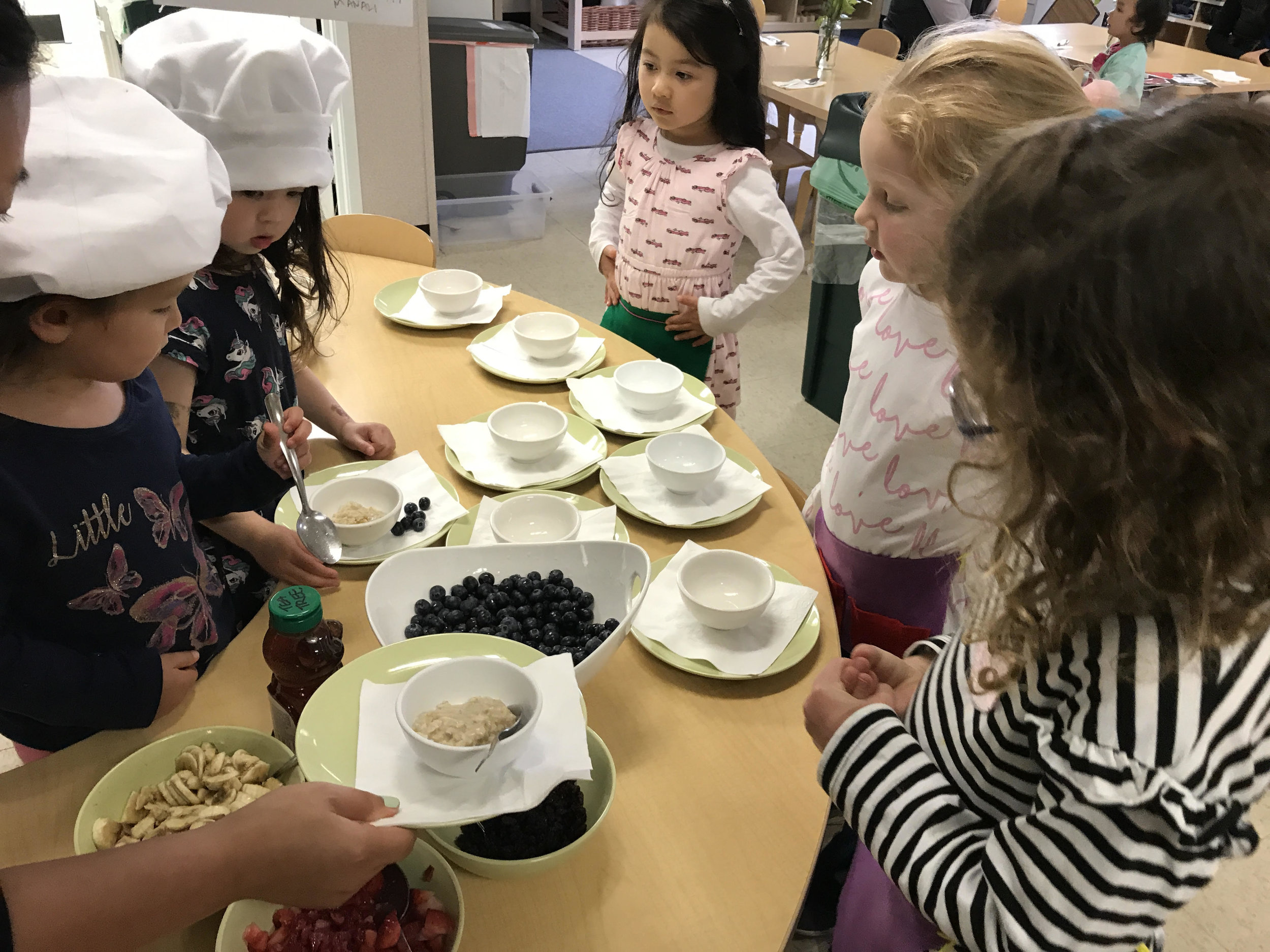 The cooks were busy in the kitchen making the dish of the day: oatmeal.