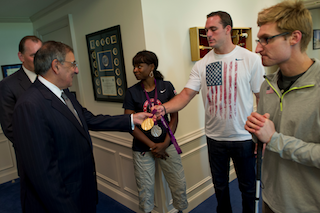 Discus thrower Jeremy Campbell at the Pentagon showing Secretary of Defense Leon Panetta his gold medal from the 2012 Paralympic Games in London