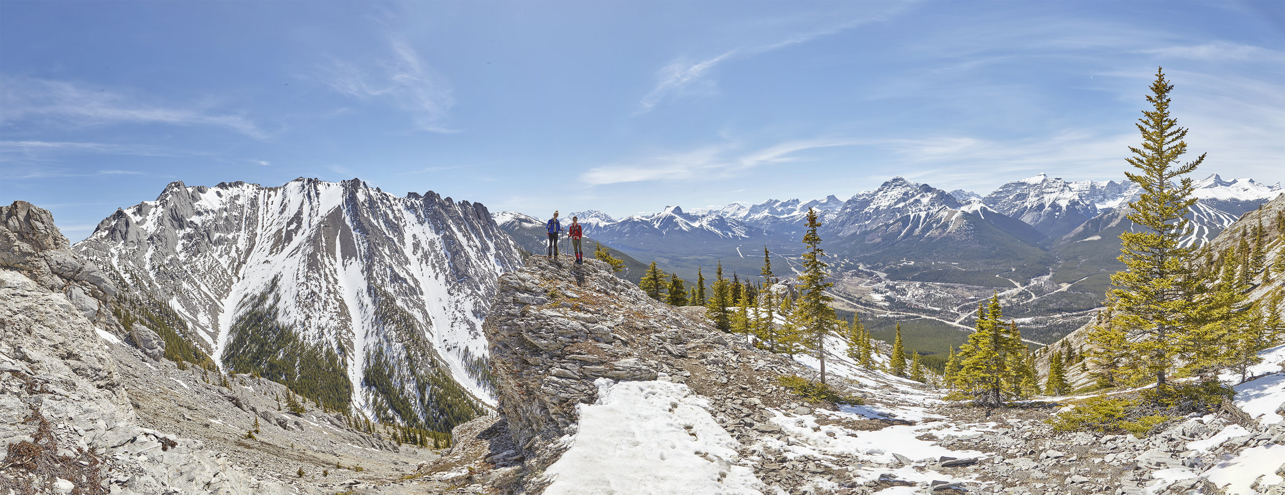Yuri and Mindy climb a pinnacle on descent. Mount Kidd and the Kananaskis Valley are below to the right.