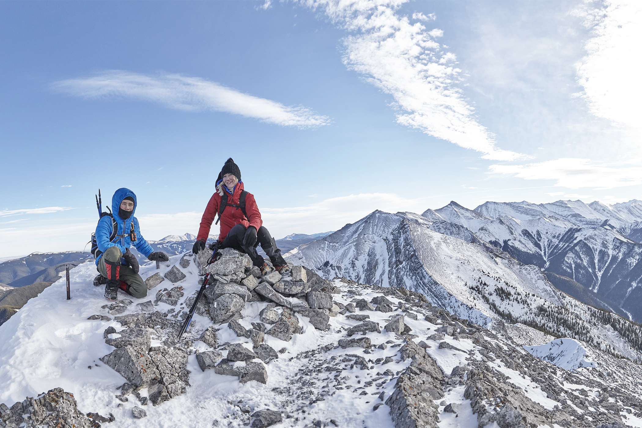 Yuri and Mindy try to not be blown of the summit by the strong wind. To the right is  Boundary Peak  and Midday Peak.
