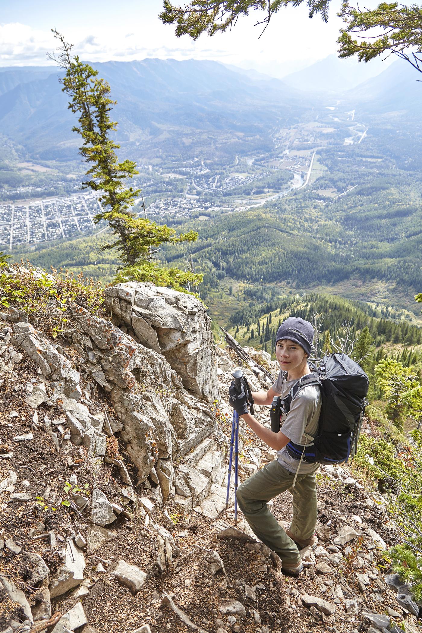 Yuri descends a rocky outcrop. Far below is the Fernie townsite.