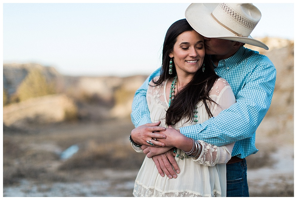 "A few weeks back I traveled to Western North Dakota to meet and photograph Kelsea and Nathan. My husband knew Nathan from his Professional Bull Riding days and their parents are old date night friends but I had never met him and felt like a semi fan-girl from watching him on TV. Have you ever met someone for the first time and felt like you've been best friends for years? That's the feeling I got from hanging out with Kelsea all evening. She was so incredibly kind and obviously good looking! When we arrived we were greeted by the normal ranch dogs and I found myself in complete awe of what they call their ""backyard"". Our night consisted of many laughs, the boys chatting ranch life, and me being in photographer Heaven. We battled the wind, timed out the lighting, and managed not to roll the ranger as we trekked up and down the hills. Thank you Kelsea and Nathan for inviting us to your home, capturing your love, and gaining new friends. I can't wait to celebrate your wedding day and watch your love story grow for many years to come!"