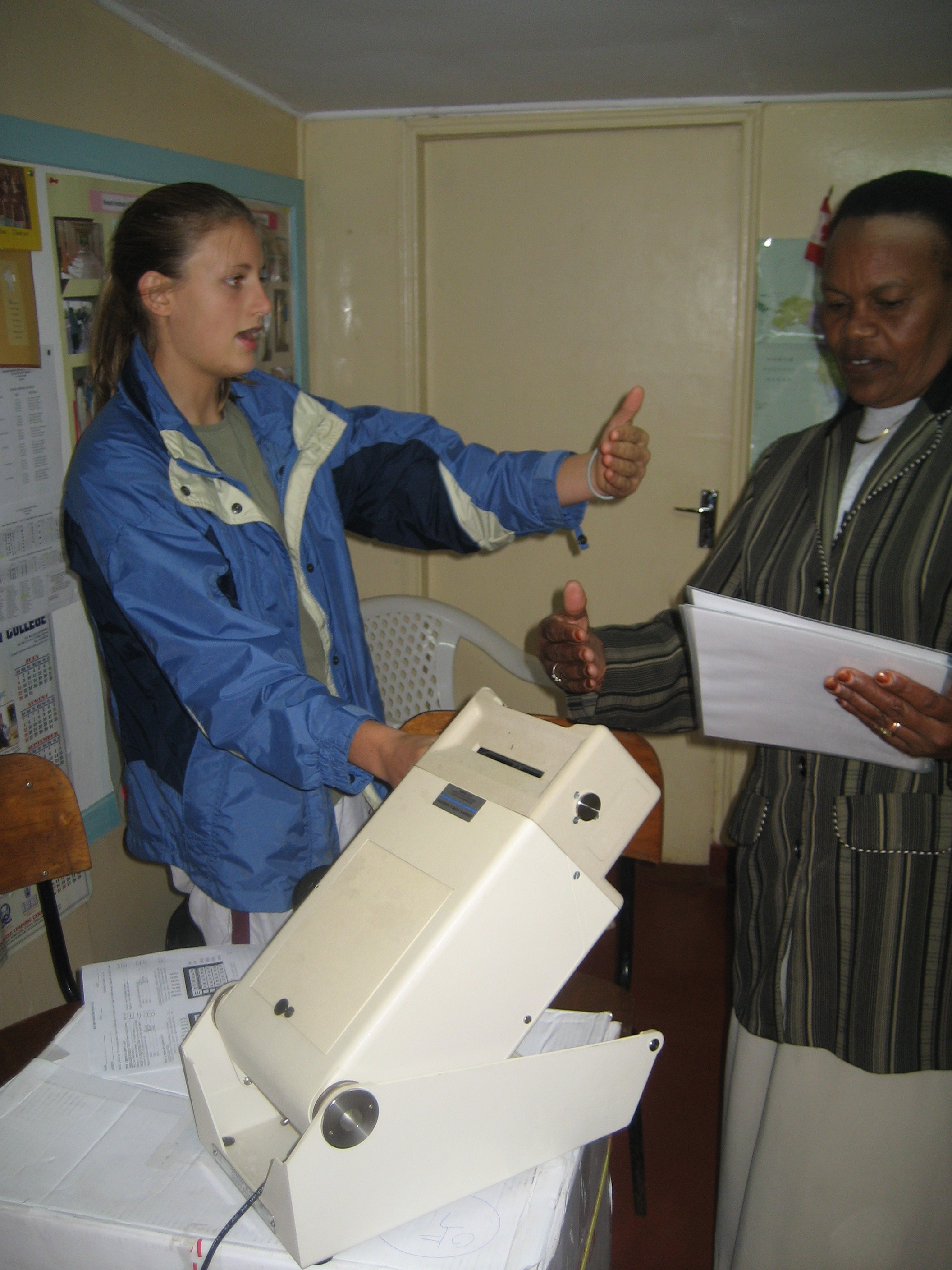 Hannah helps a nurse learn how to work the new vision testing machine at the Sugarbaker Memorial Clinic.